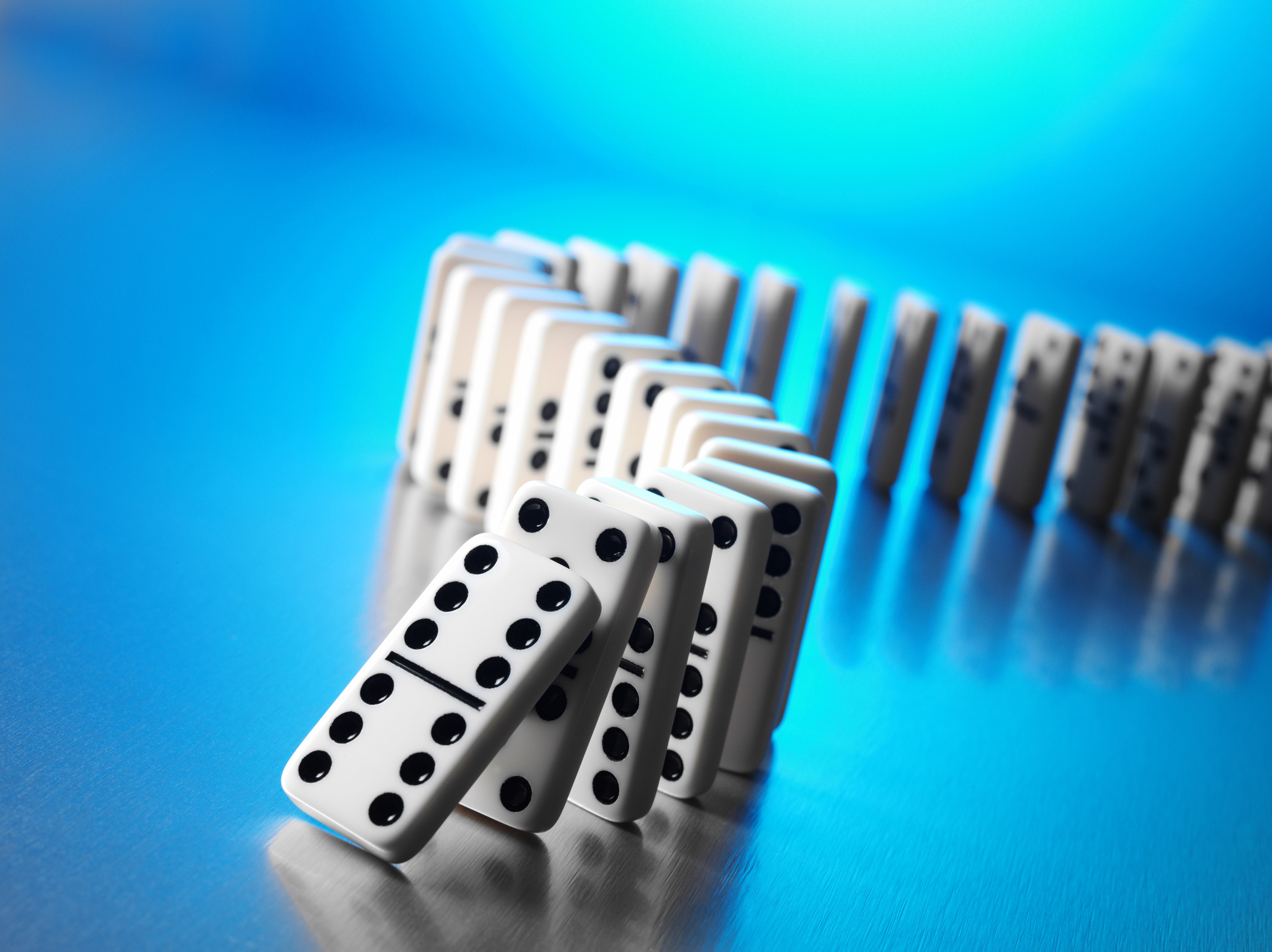 Domino effect on a stainless steel background with blue lighting and copy space.Click on the link below to see more of my sport and business images